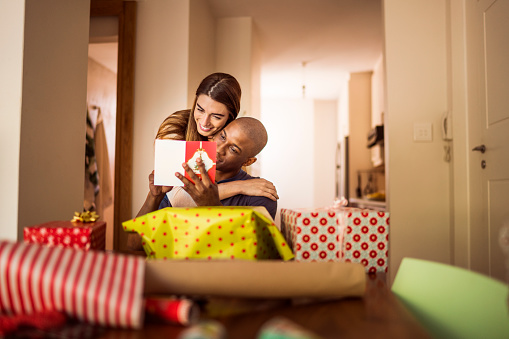 A photo of woman embracing boyfriend. Man and woman are reading greeting card. They are at home during Christmas.