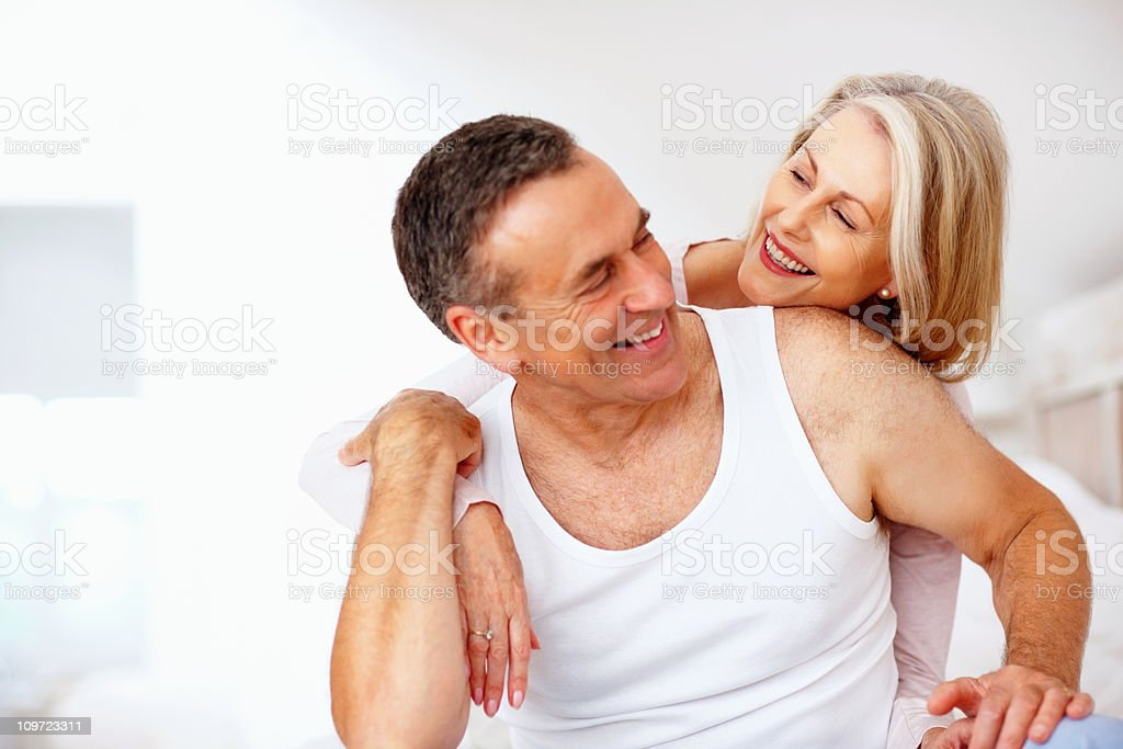 Woman embracing husband from back royalty-free stock photo