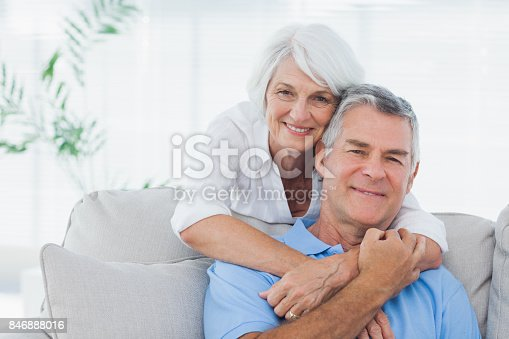 istock Woman embracing husband sitting on the couch 846888016