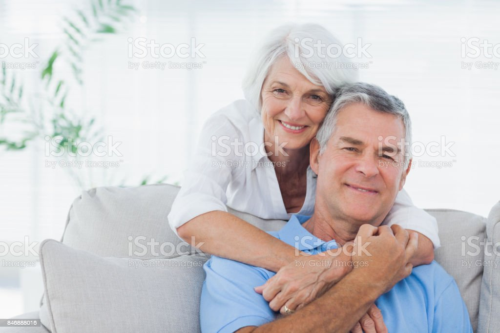 Woman embracing husband sitting on the couch stock photo