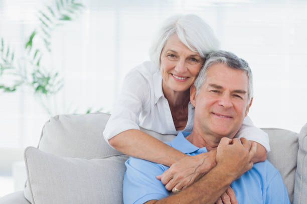 Woman embracing husband sitting on the couch Mature woman embracing husband sitting on the couch 60 64 years stock pictures, royalty-free photos & images