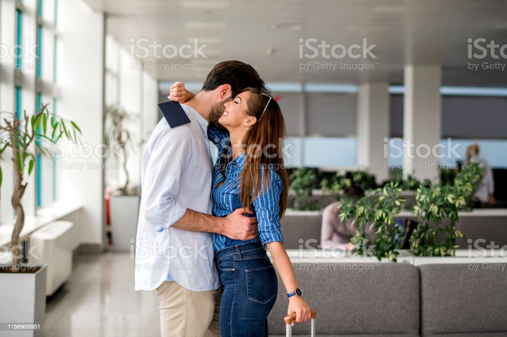 Woman Embracing Man At Airport After Long Separation Stock