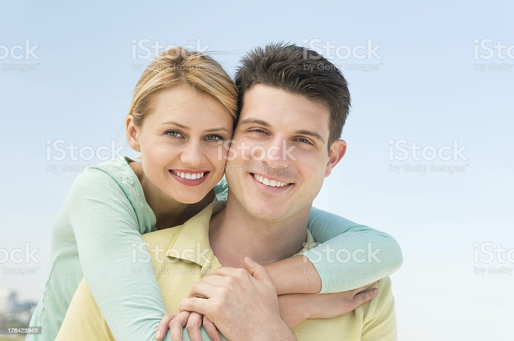 Woman Embracing Man From Behind Against Clear Sky stock photo