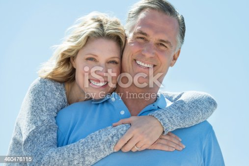 istock Woman embracing man from behind under clear sky 460476115
