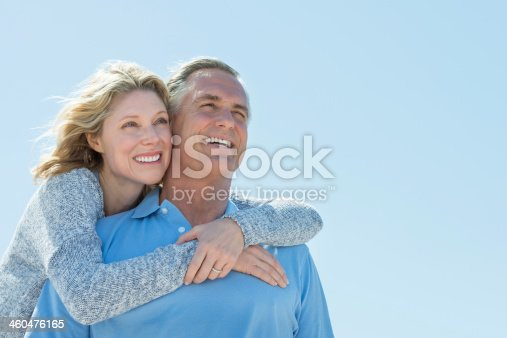 istock Woman Embracing Man From Behind While Looking Away Against Sky 460476165