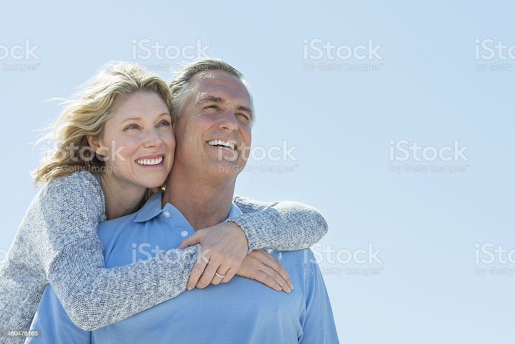 Woman Embracing Man From Behind While Looking Away Against Sky stock photo