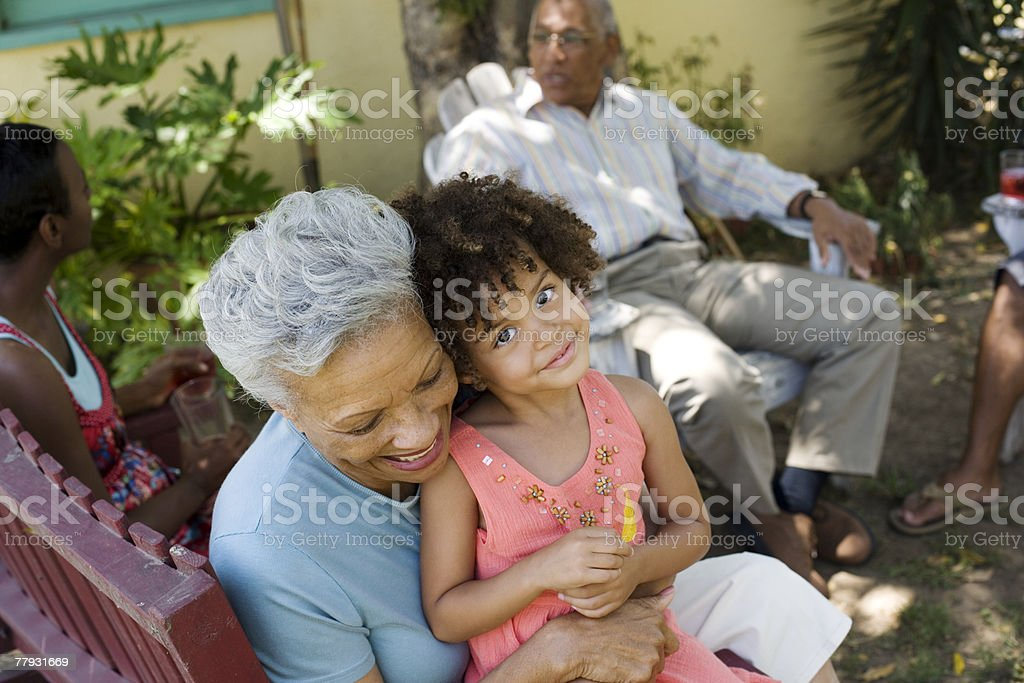 Woman embracing young girl with people in background stock photo