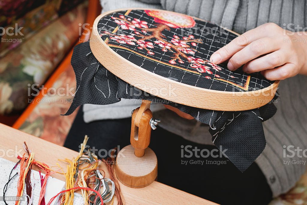 woman embroider  tree of cherry stock photo
