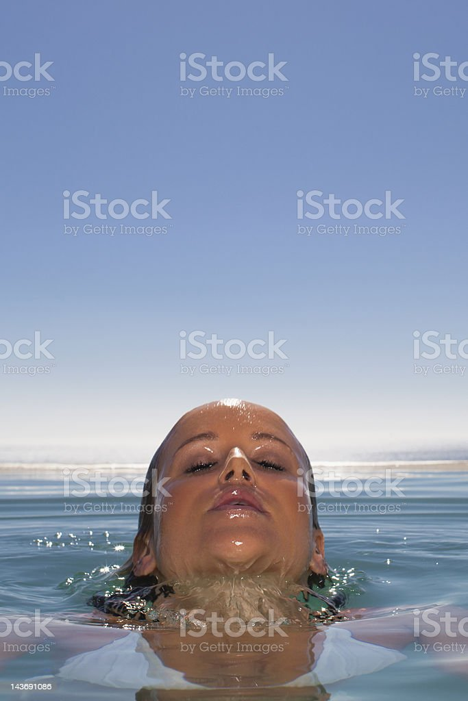 Woman emerging from swimming pool stock photo