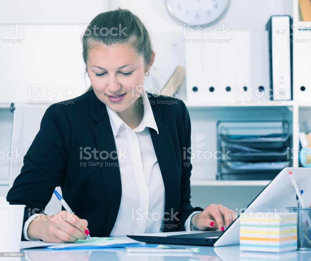 Woman employee is working with documents and laptop stock photo