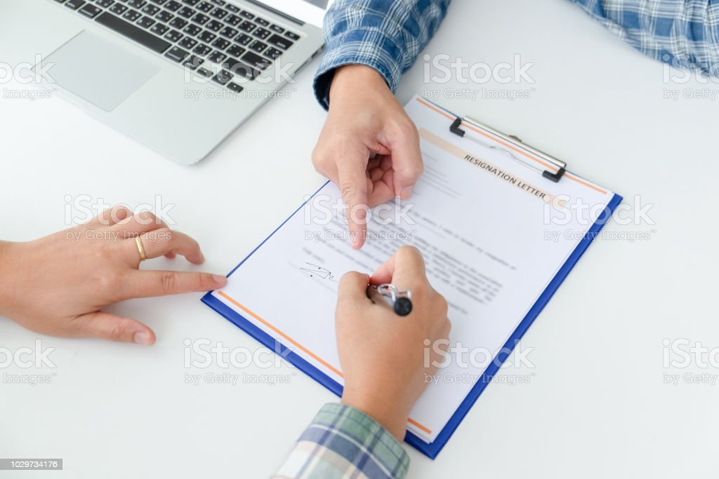 Woman employee writing a letter of resignation on the white table. The concept for forced resign. stock photo