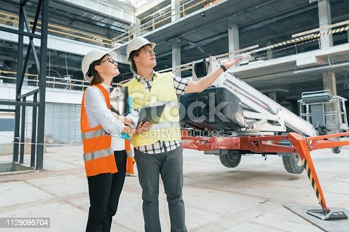 istock Woman engineer and man builder at construction site. Building, development, teamwork and people concept 1129095704