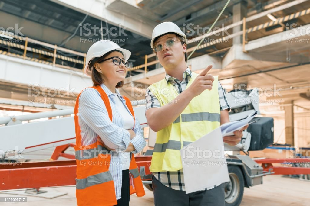Woman engineer and man builder at construction site. Building,...