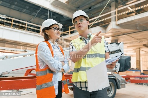 1129095769 istock photo Woman engineer and man builder at construction site. Building, development, teamwork and people concept 1129095747