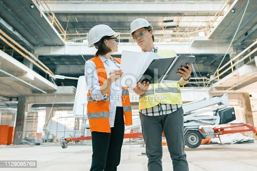 681242254 istock photo Woman engineer and man builder at construction site. Building, development, teamwork and people concept 1129095769