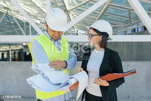 1129095769 istock photo Woman engineer and man builder at construction site. Building, development, teamwork and people concept 1130462616
