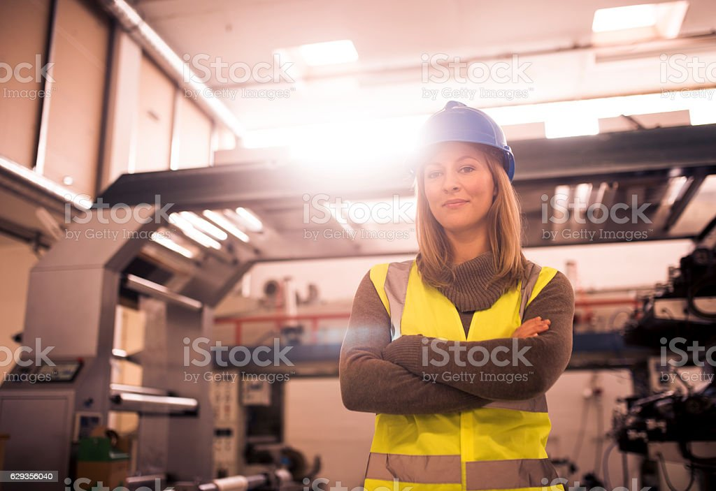 Young woman is standing in a production hall with arms crossed. She...