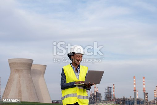 istock Woman engineer checking the data of oil refinery. 935329624