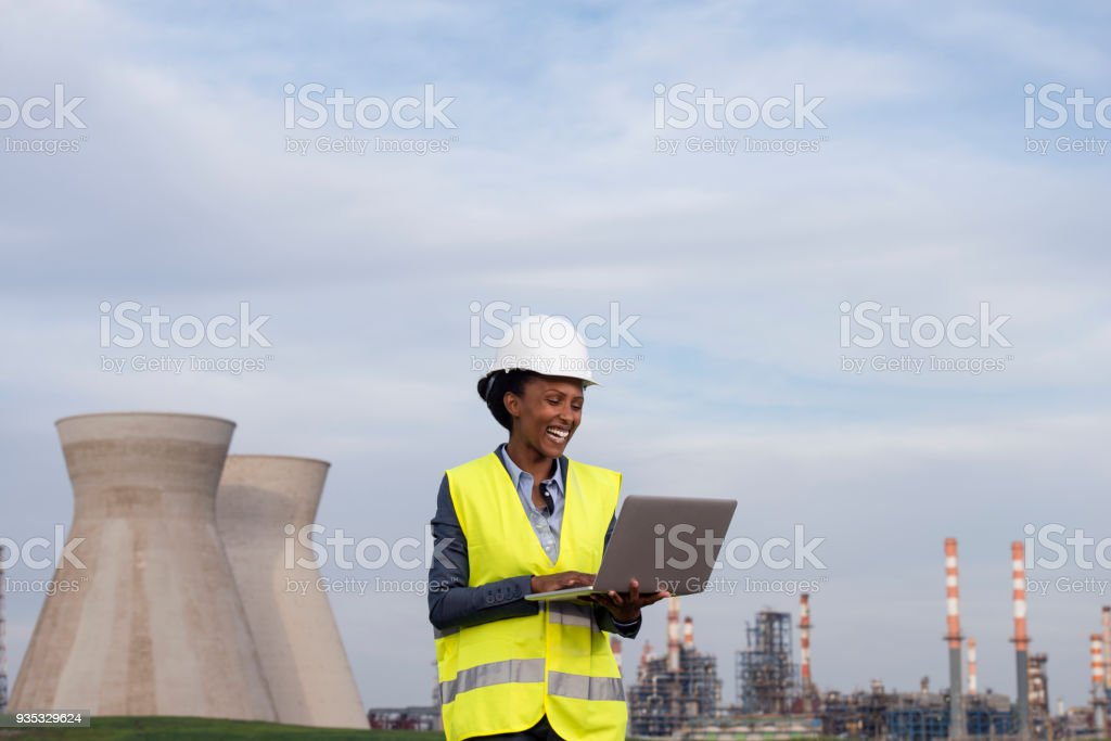 Woman engineer checking the data of oil refinery. stock photo