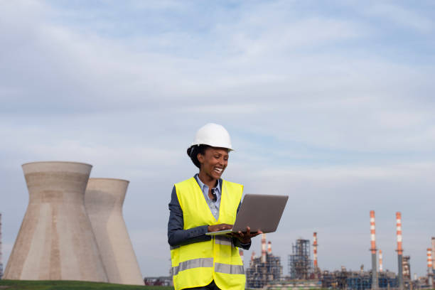Woman engineer checking the data of oil refinery. Woman engineer checking the data of the oil refinery, using a laptop computer. nuclear power station stock pictures, royalty-free photos & images