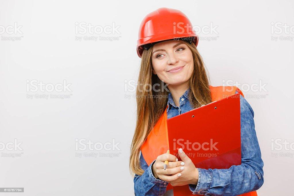 Woman engineer construction builder in helmet. Woman construction worker builder structural engineerin in orange vest red hard helmet holds pen file pad. Safety in industrial work. Studio shot Adult Stock Photo