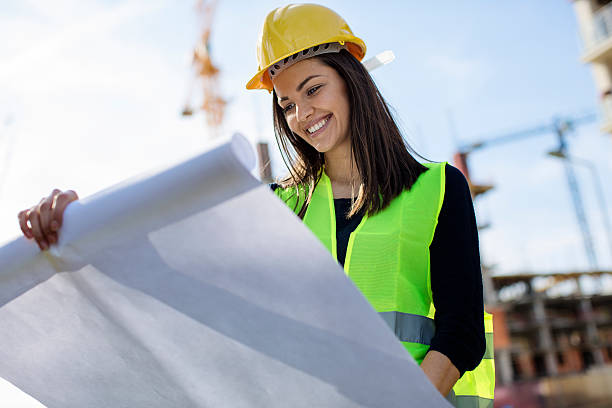 Woman engineer looking at blueprints stock photo