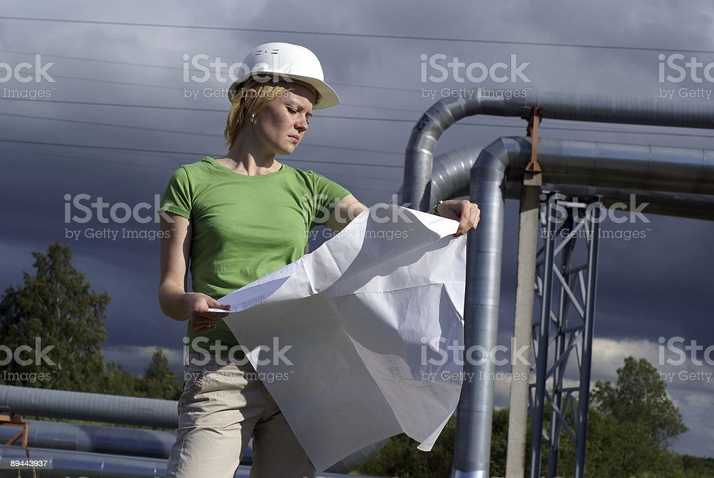Woman engineer with white safety hat drawings industrial pipelines royalty-free stock photo