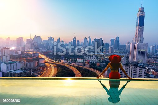 istock woman enjoy city light in background in swimming pool on rooftop of building 960098280