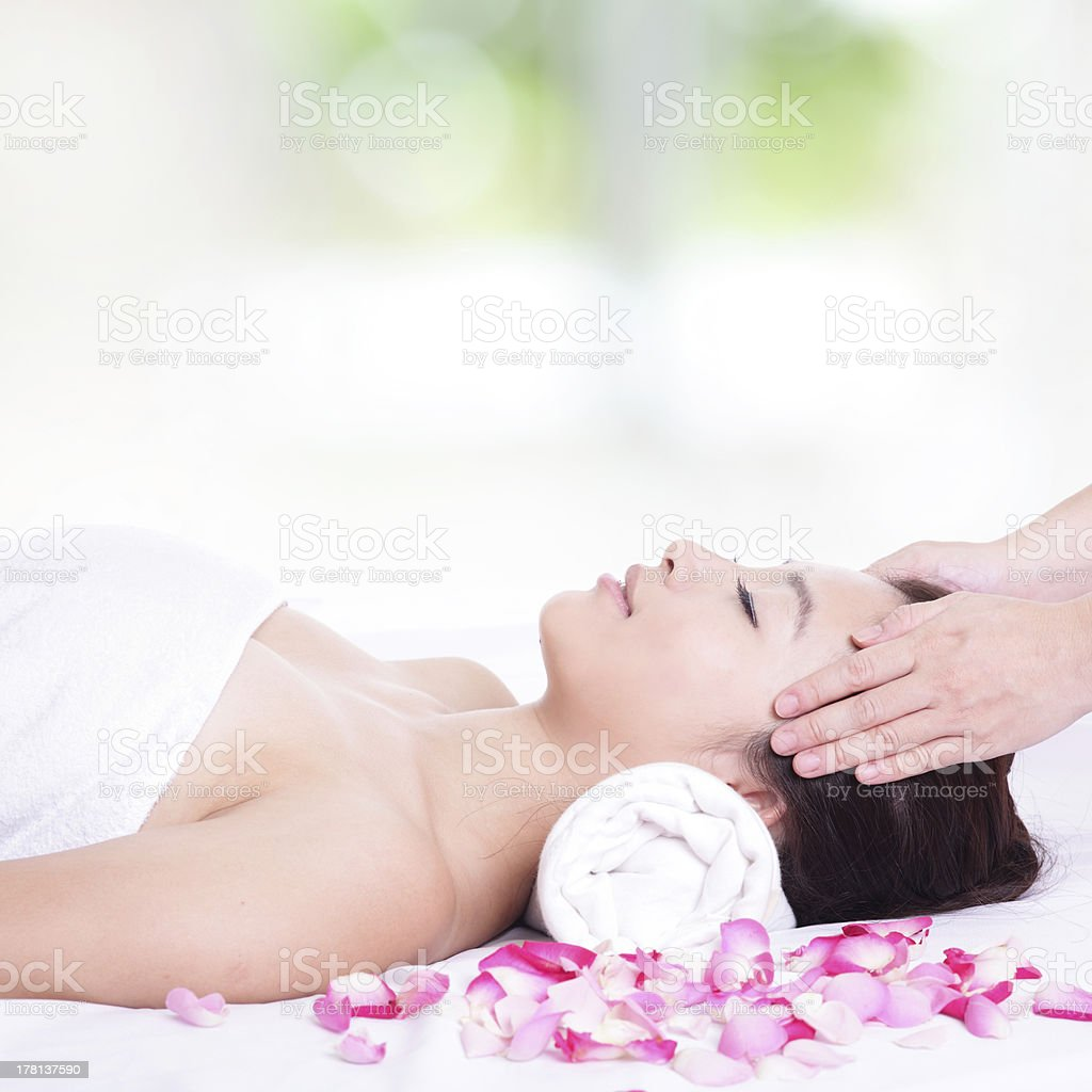 woman enjoy face and head massage at spa stock photo