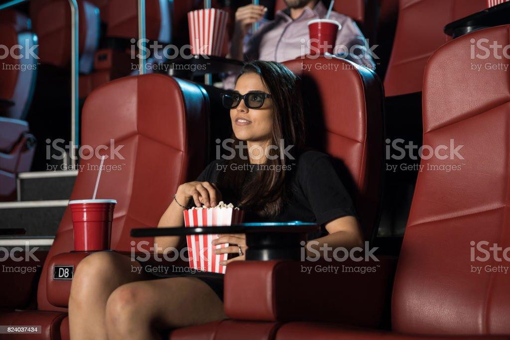 Woman enjoying a 3d movie with popcorn stock photo