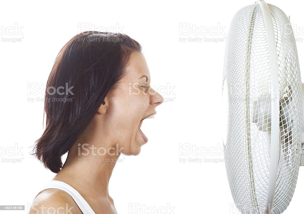 Woman enjoying a cooling fan, on a white background  stock photo