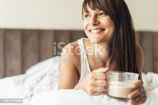 Happy smiling Woman Enjoying a cup of coffee in bed