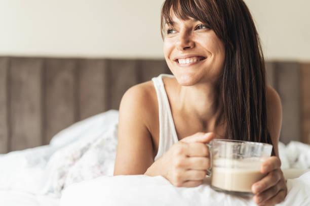 frau bei einer tasse kaffee im bett - aufwachen stock-fotos und bilder
