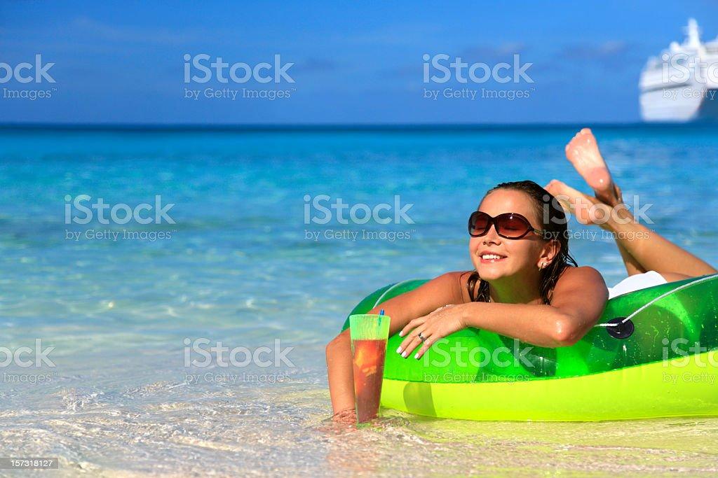 woman enjoying a drink on the beach stock photo
