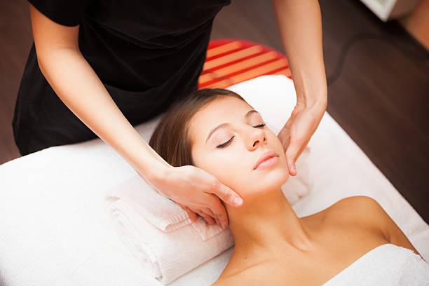 Mujer disfrutando de un masaje facial - foto de stock