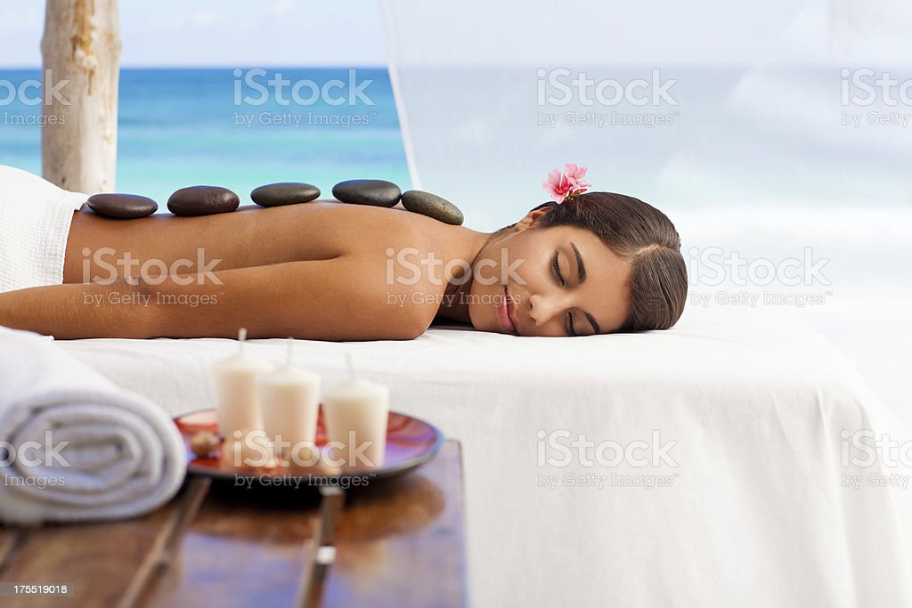 Woman enjoying a massage by the beach royalty-free stock photo