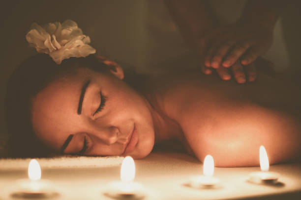 woman enjoying a massage treatment. - thai massage stock photos and pictures