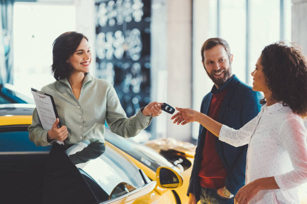 Woman enjoying a new car Young man surprising his wife with buying a new car car salesperson stock pictures, royalty-free photos & images
