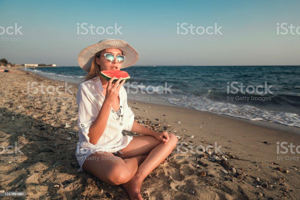 Vrouw die van een plak van watermeloen op het strand geniet - Royalty-free Alleen volwassenen Stockfoto