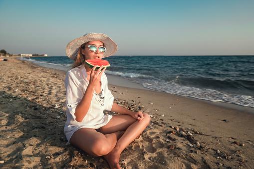 Vrouw Die Van Een Plak Van Watermeloen Op Het Strand Geniet Stockfoto en meer beelden van Alleen volwassenen