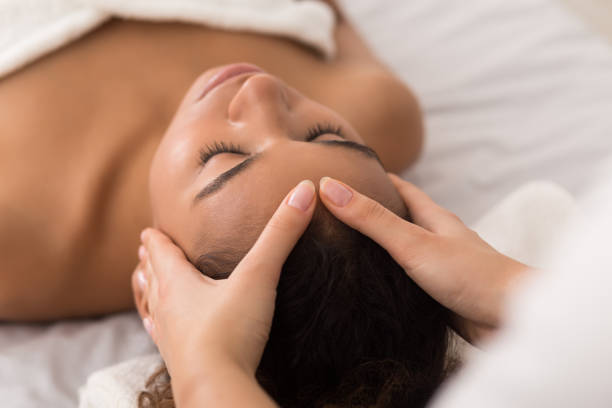 woman enjoying anti aging facial massage in spa salon - massage stock pictures, royalty-free photos & images