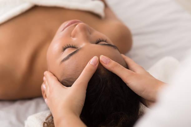 Woman enjoying anti aging facial massage in spa salon African-american woman enjoying anti aging facial massage in spa salon spa stock pictures, royalty-free photos & images