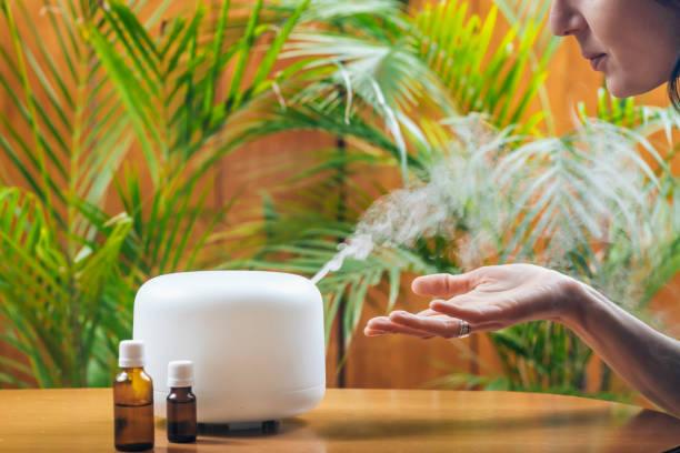 自宅エッセンシャルオイルディフューザーまたは空気加湿器からアロマセラピースチームの香りを楽しむ女性 - 加湿器 ストックフォトと画像