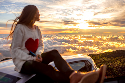 Young woman in sweater with heart shape enjoying beautiful cloudscape sitting on the car roof above the clouds on the sunrise. Image focused on the clouds