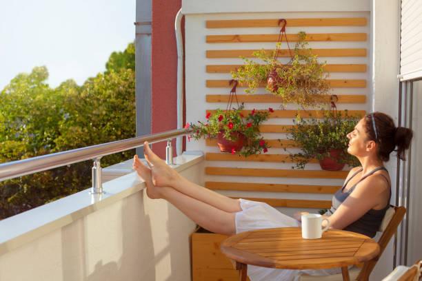 woman enjoying beautiful morning sun on her balcony - abbronzarsi foto e immagini stock