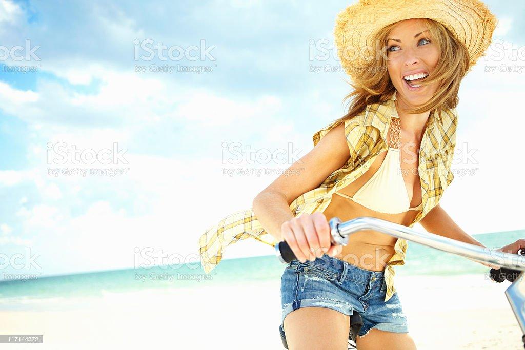 Woman enjoying bicycle ride on beach royalty-free stock photo