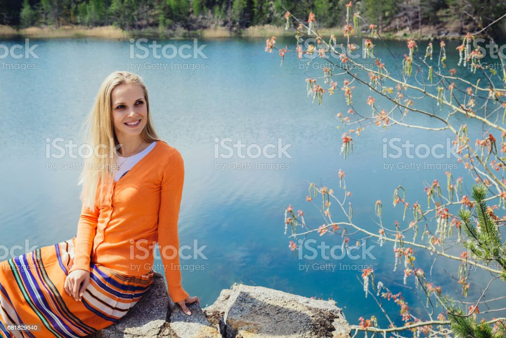 woman enjoying blue lake water on the high cliff in summer stock photo