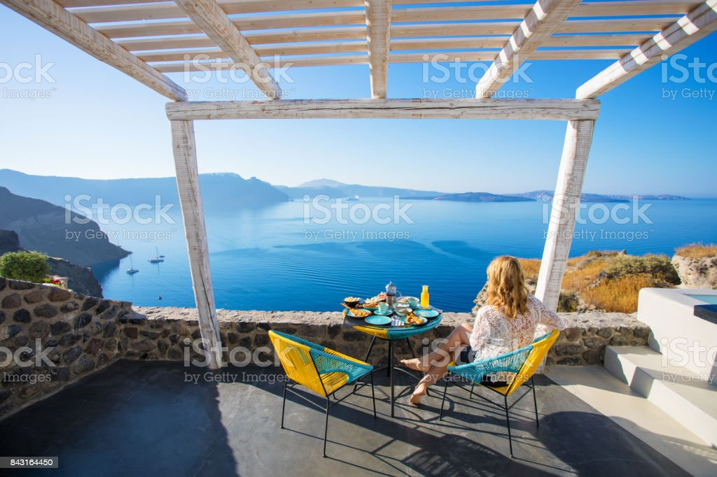Woman enjoying breakfast with beautiful view over Santorini stock photo