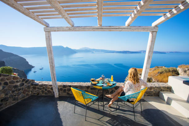 Woman enjoying breakfast with beautiful view over Santorini stock photo