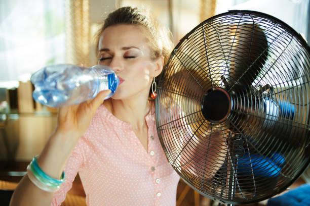 Frau genießt die Brise vor dem Arbeitsfan und dem Trinkwasser – Foto